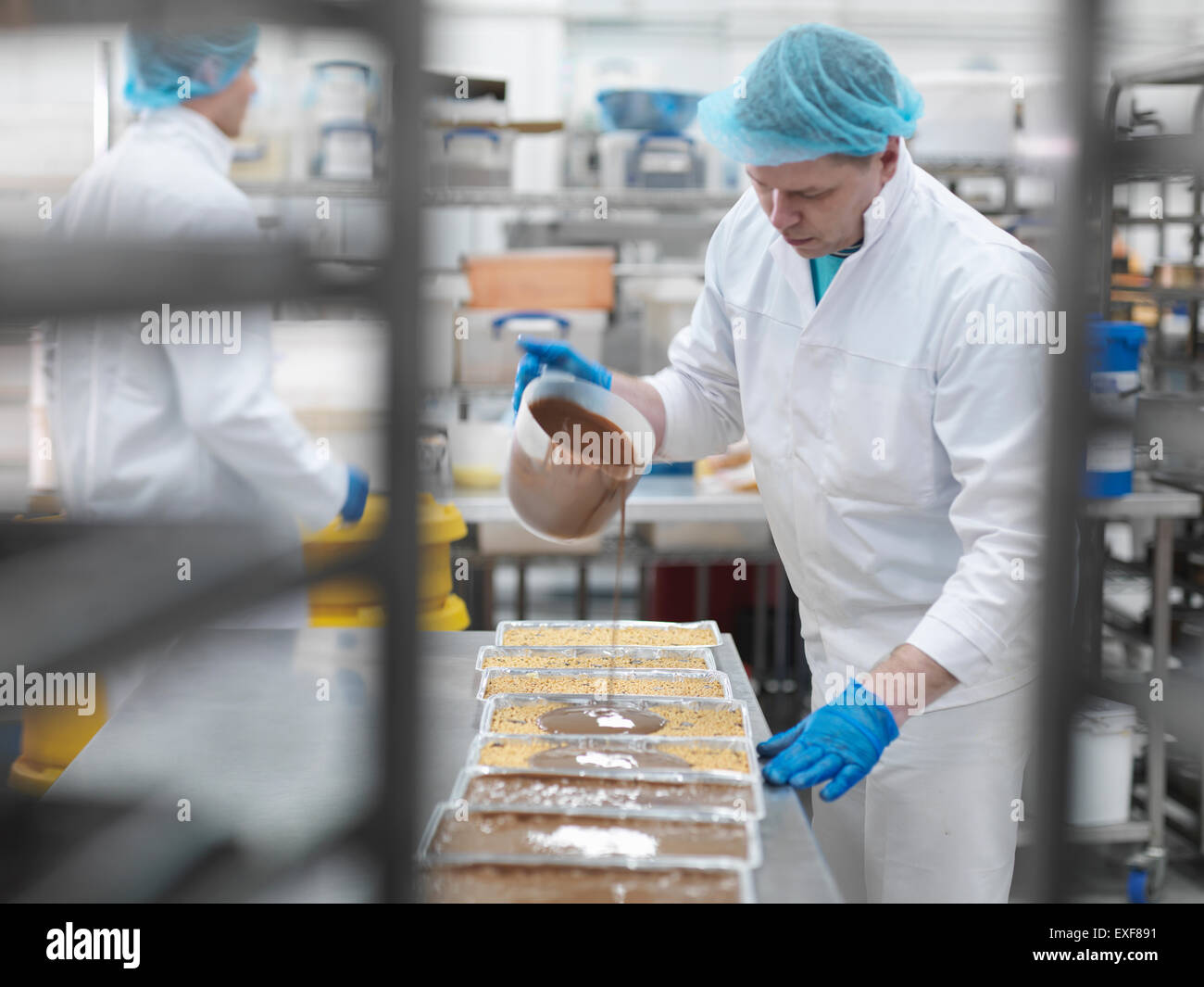 Male worker pouring chocolate in cake factory - Stock Image