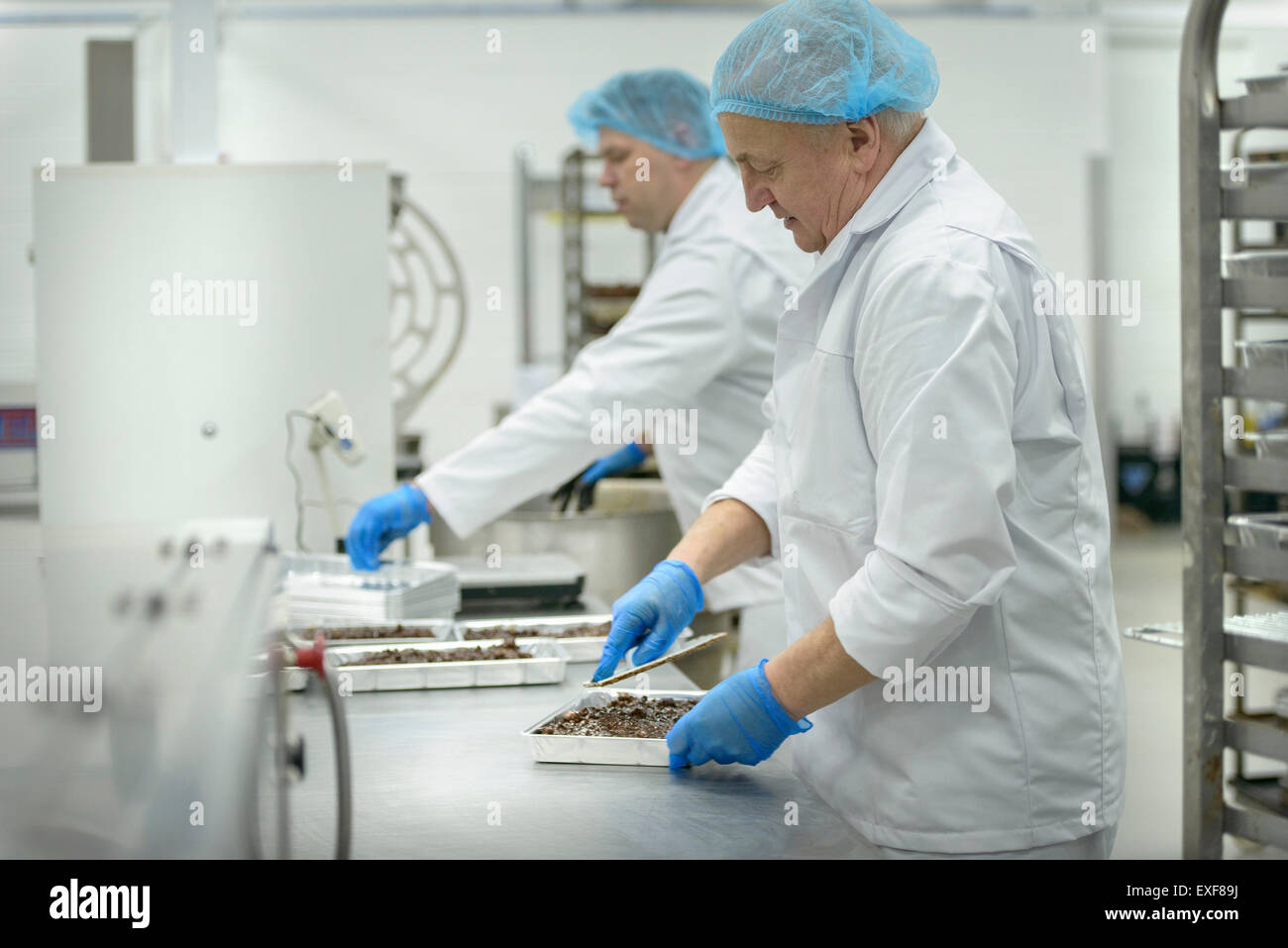 Bakers prepare trays of product in cake factory - Stock Image
