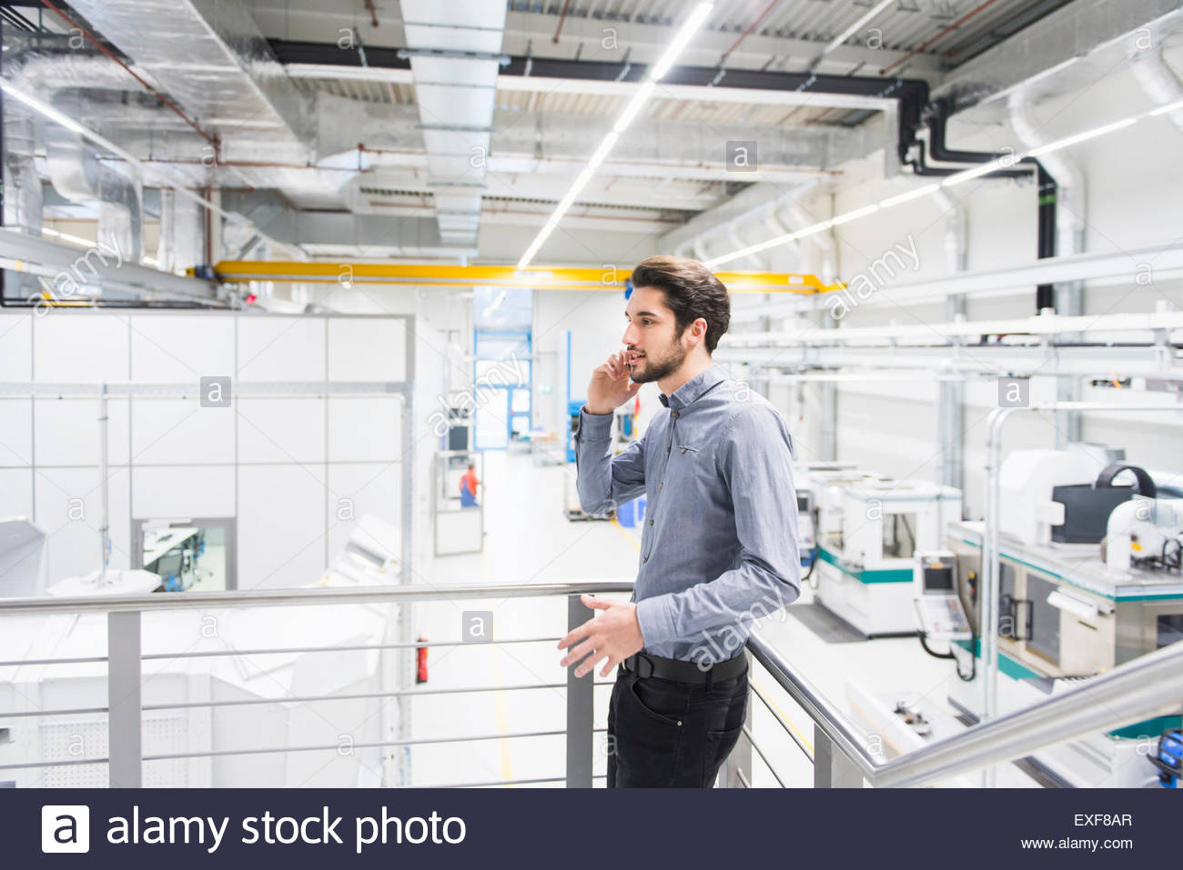 Male worker using mobile phone in tool manufacturing plant - Stock Image