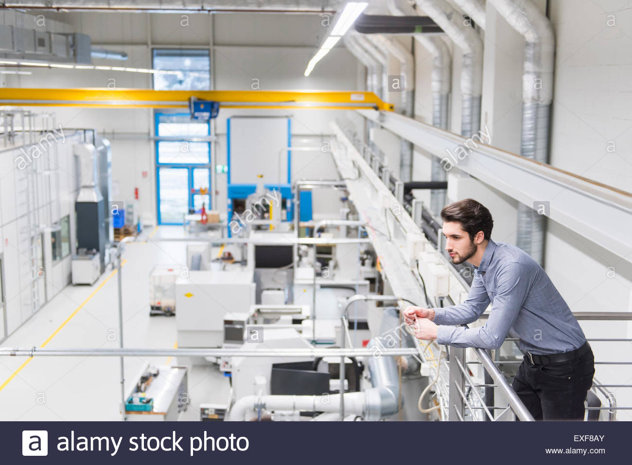 Male worker standing on balcony at tool manufacturing plant - Stock Image