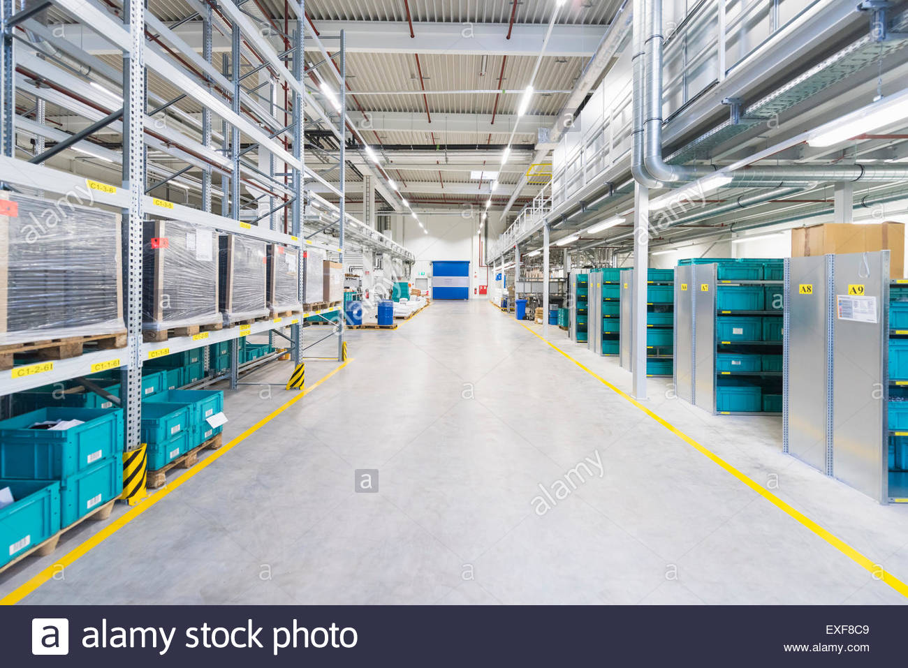 Aisle of industrial warehouse with storage shelving - Stock Image