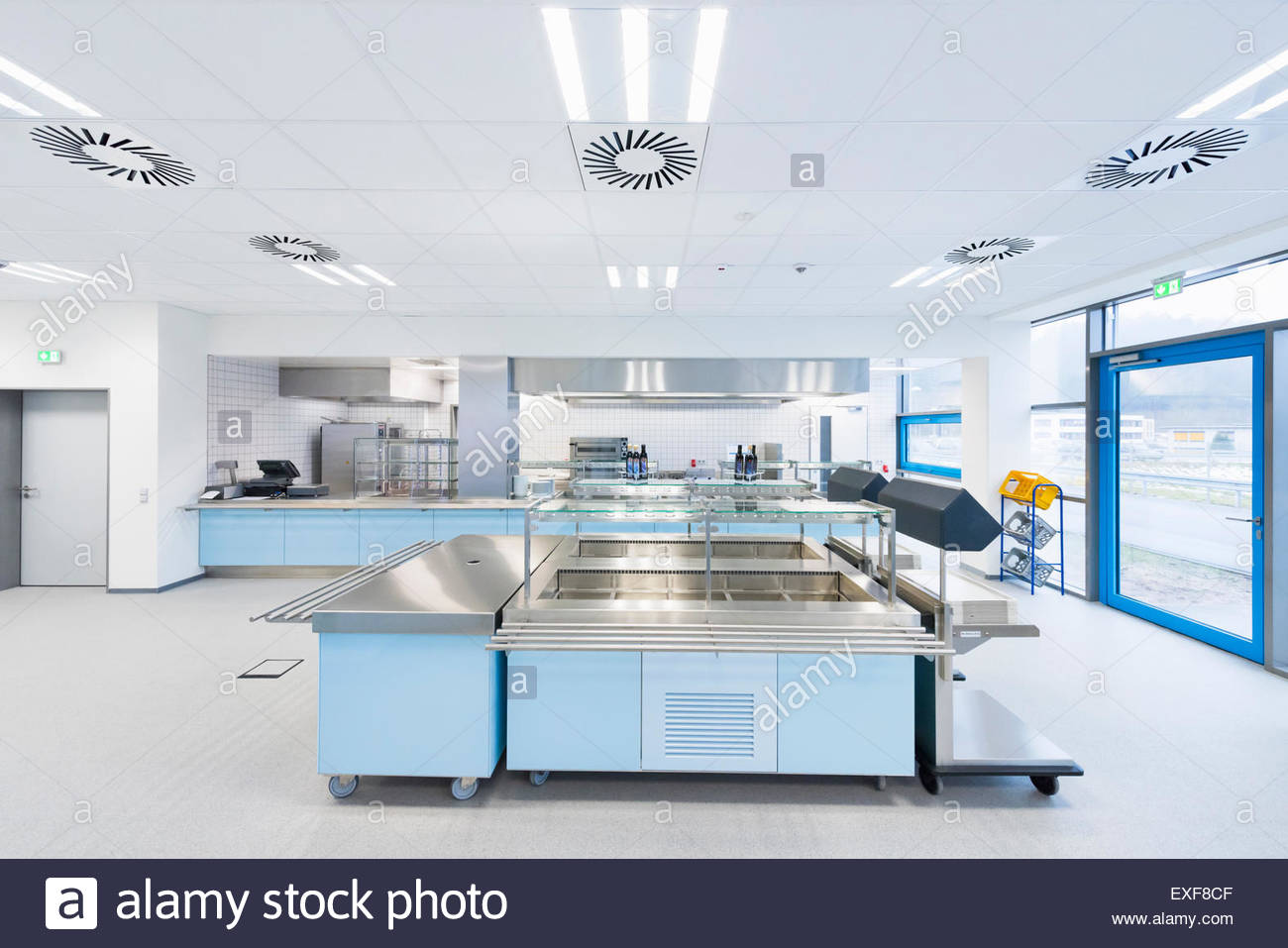 Empty factory canteen with serving counters - Stock Image