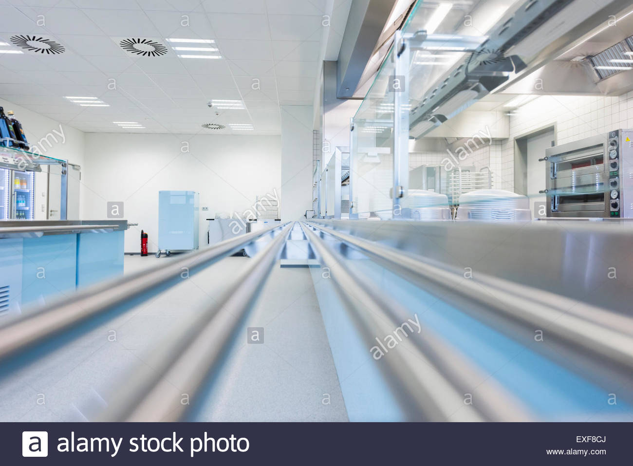 Empty factory canteen with tray rails and serving hatch - Stock Image
