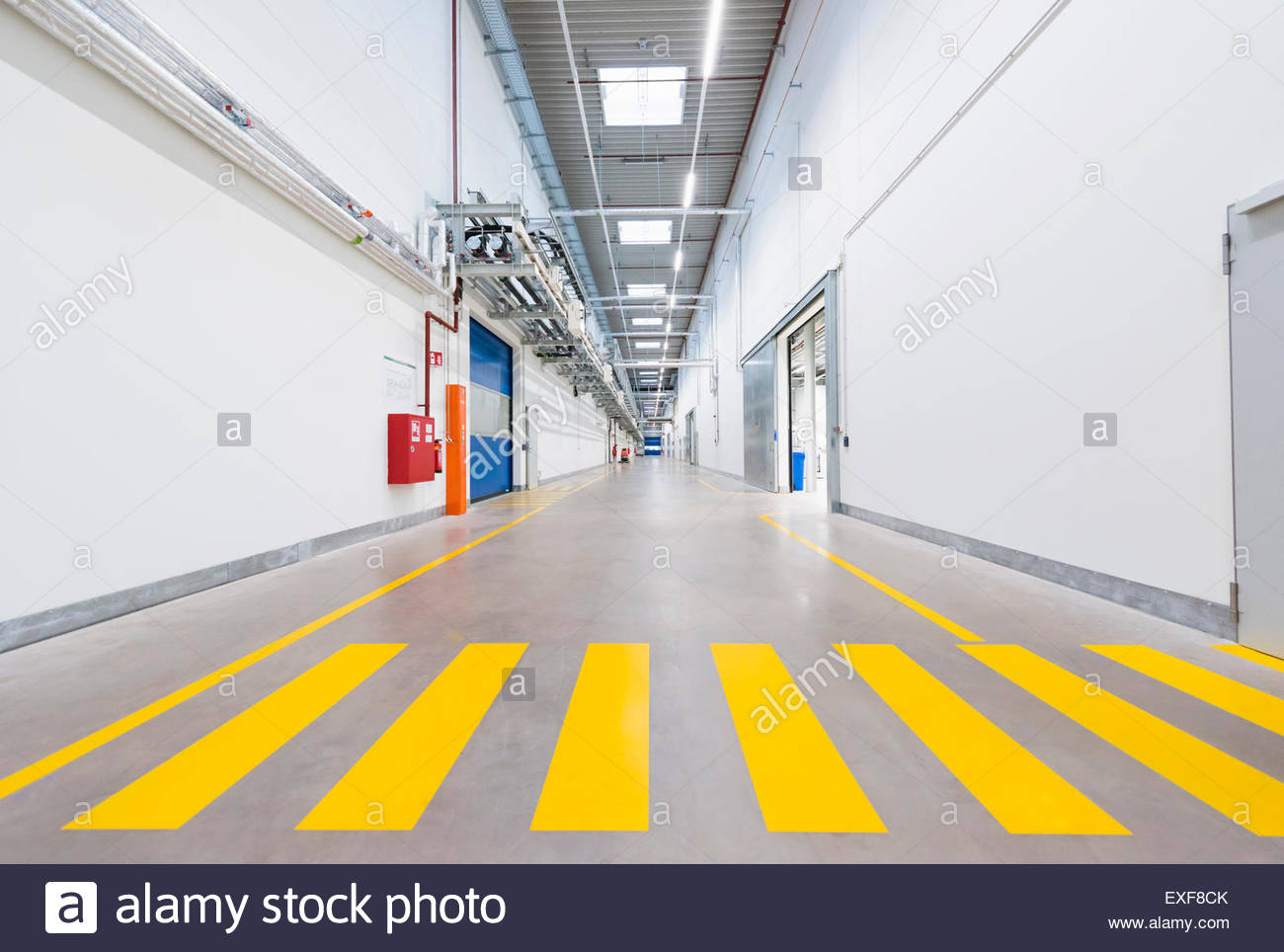 Factory corridor with yellow pedestrian crossing - Stock Image
