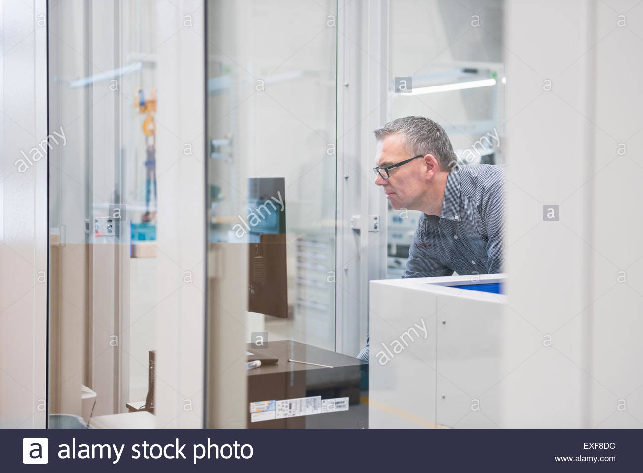 Factory worker monitoring computer screen in factory - Stock Image