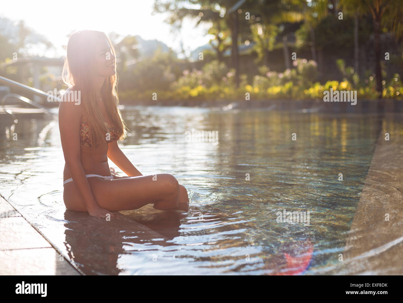 Young woman in bikini sitting in swimming pool, Panay Island, Visayas, Philippines - Stock Image