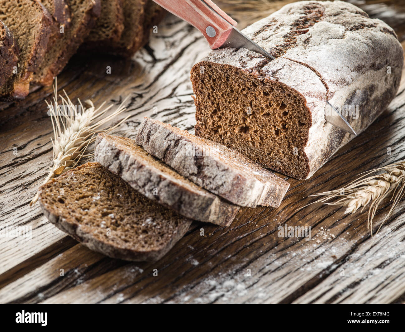 Sliced black bread on the old wooden plank. - Stock Image