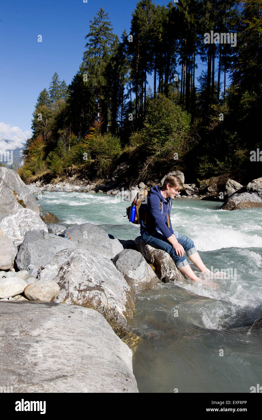 Male hiker sitting on rock with bare feet in river, Lauterbrunnen, Grindelwald, Switzerland - Stock Image