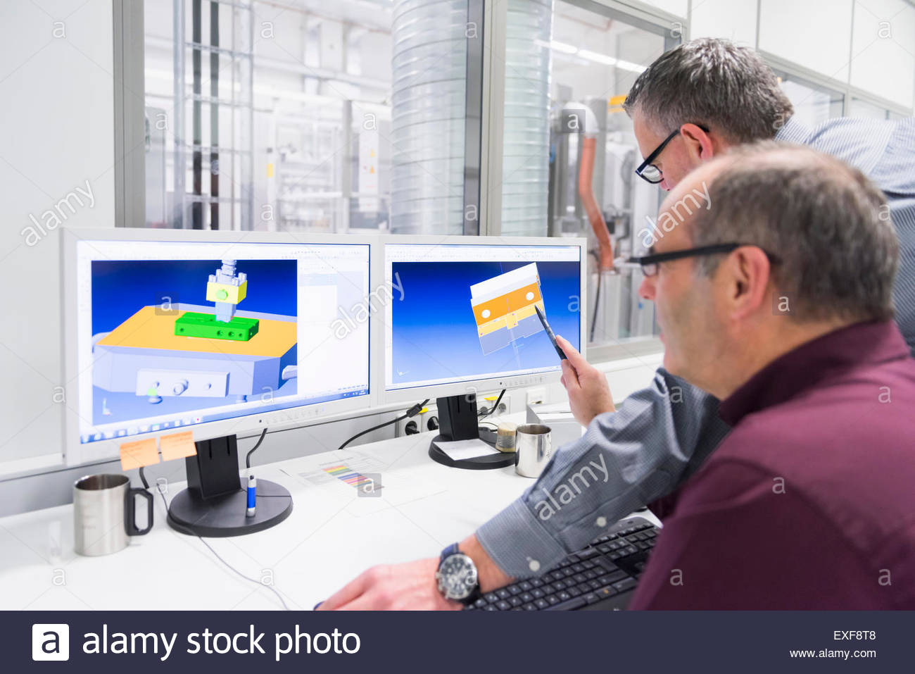 Manager and factory engineer looking at computer designs - Stock Image
