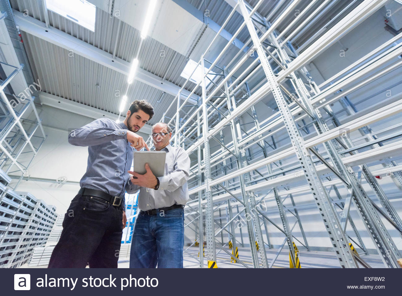 Low angle view of businessman meeting worker in factory warehouse - Stock Image