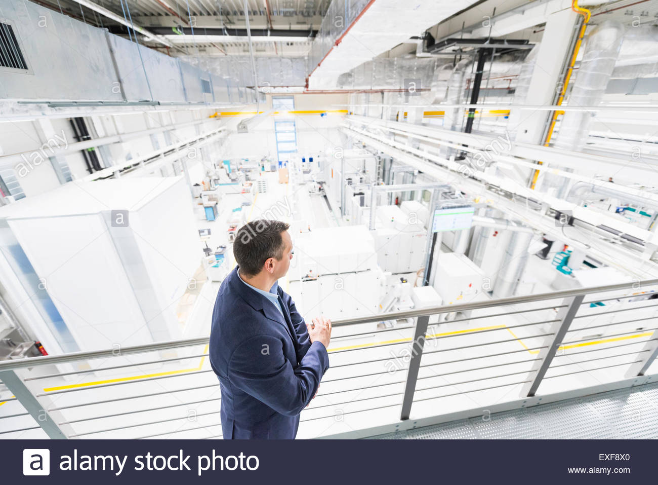 High angle view of manager looking down on factory - Stock Image