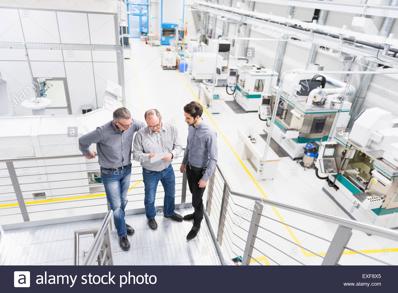 Engineers discussing notes on factory stairway - Stock Image