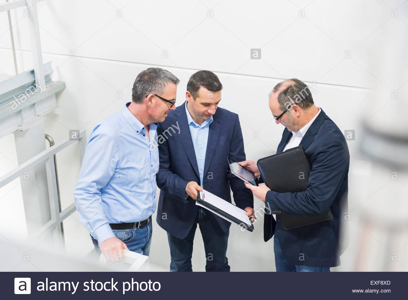 Businessmen and manager notes and digital tablet on factory stairway - Stock Image