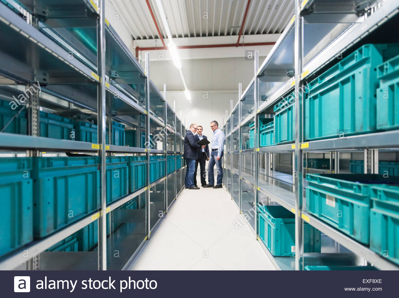 Businessmen and manager meeting in empty factory warehouse - Stock Image
