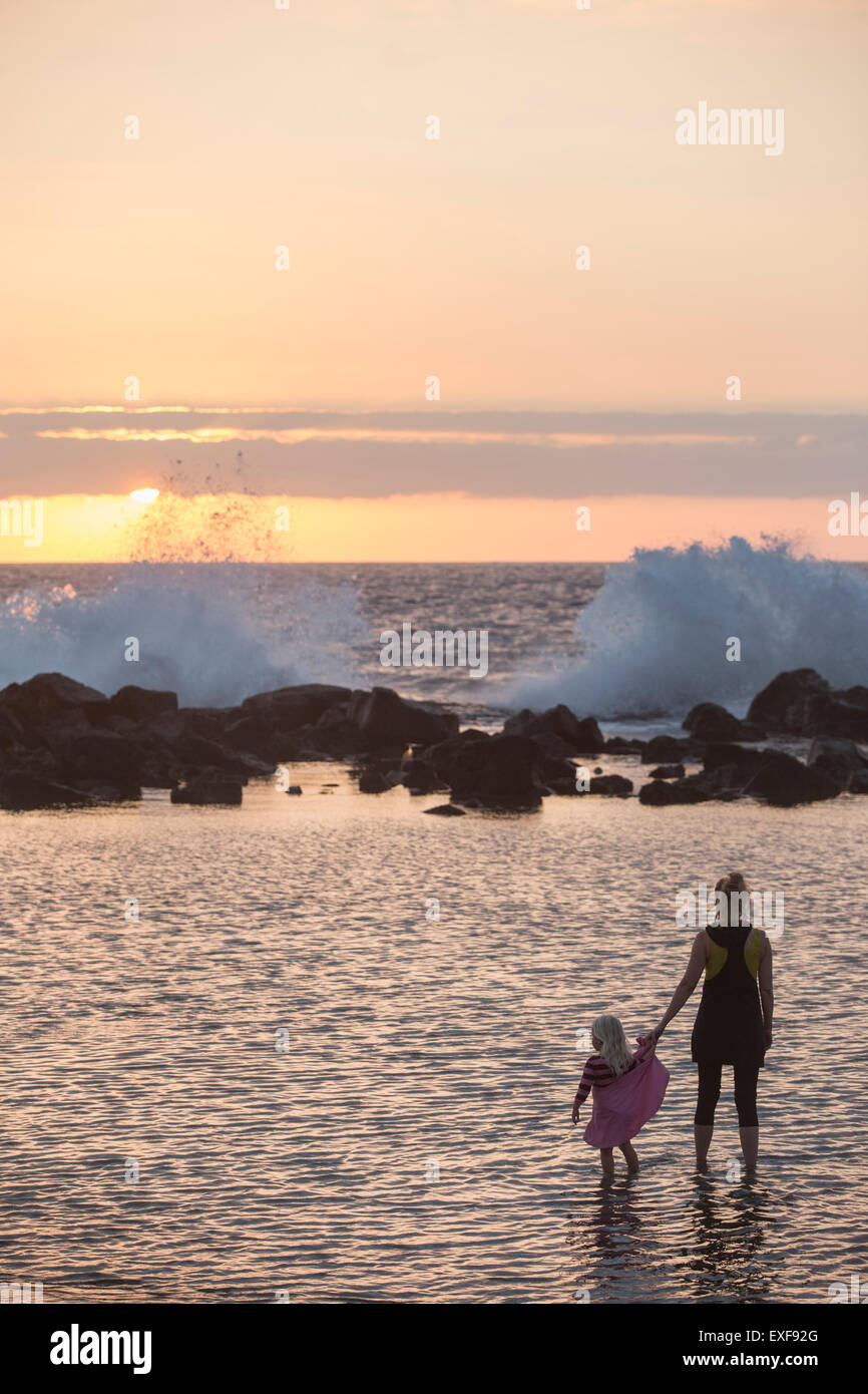 Silhouetted female toddler and mother paddling in sea looking out at waves splashing, Kona, Hawaii, USA Stock Photo