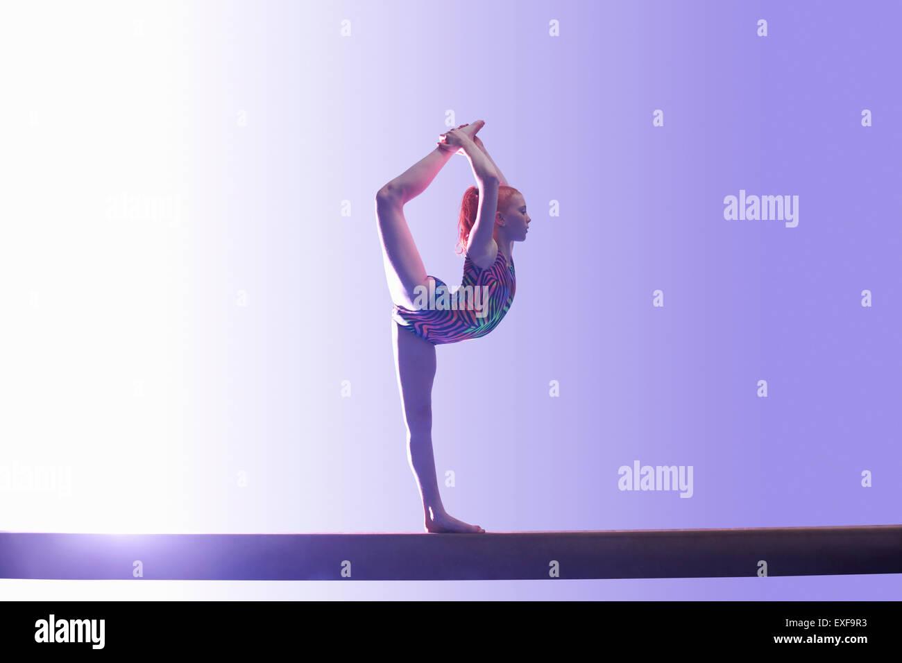 Young gymnast performing on balance beam - Stock Image