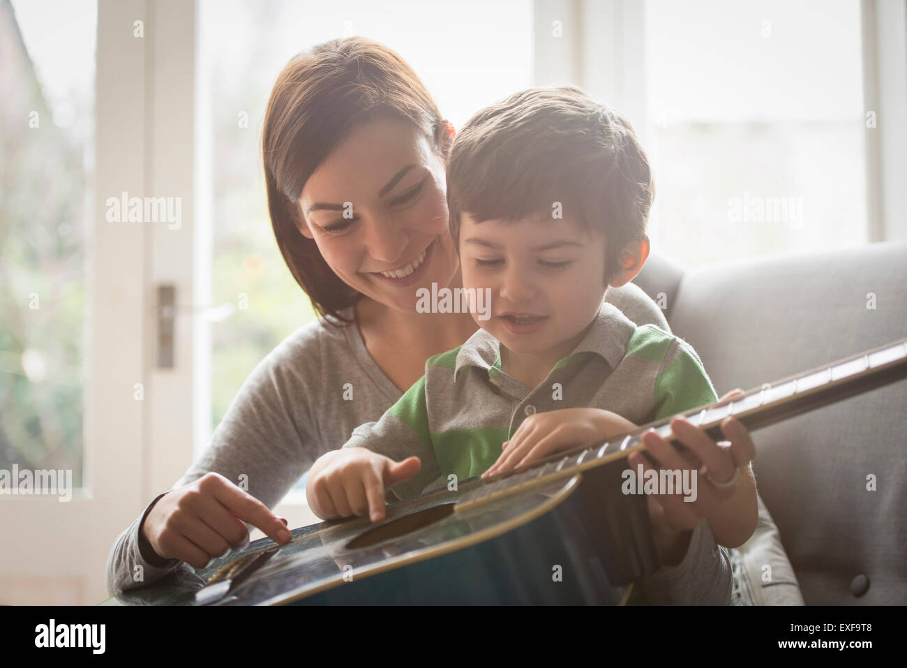 Boy sitting on mother's lap and learning to play guitar Stock Photo
