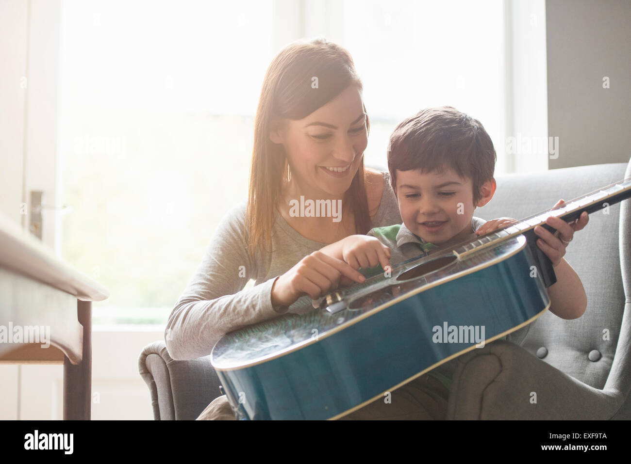 Boy sitting on mother's lap in sunlit room and learning to play guitar - Stock Image