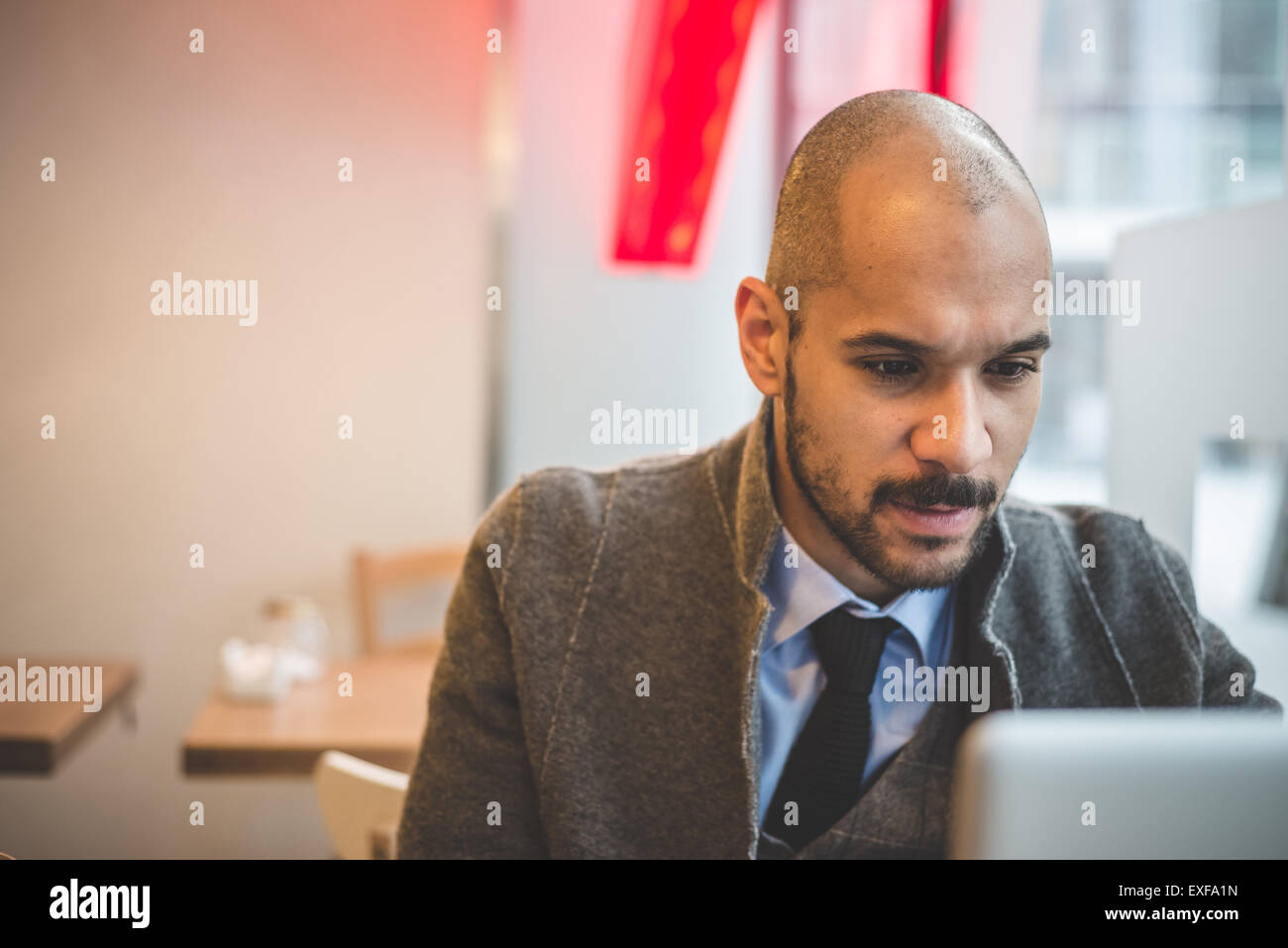 Businessman sitting in cafe using laptop - Stock Image
