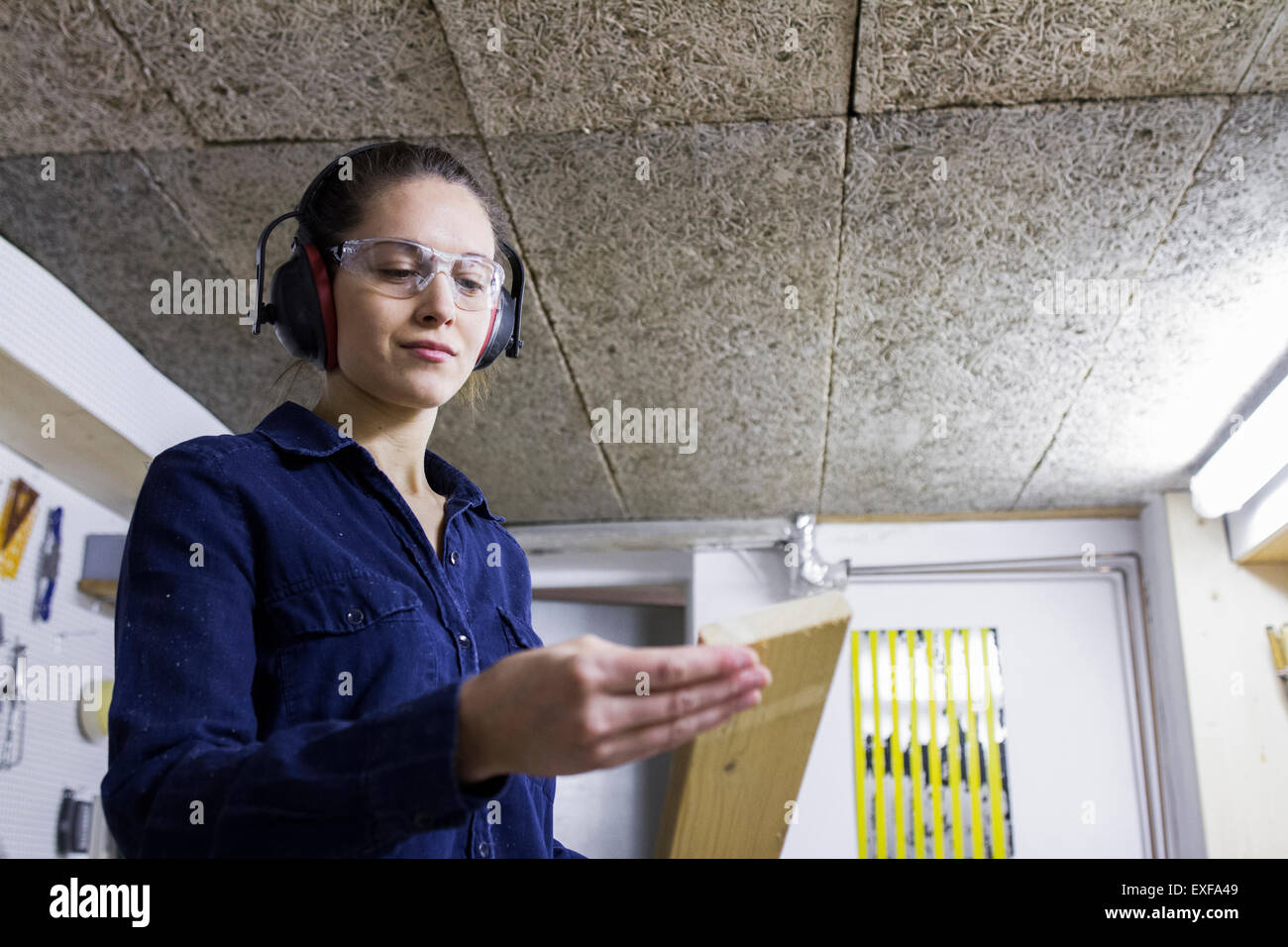 Young female carpenter examining timber in workshop - Stock Image