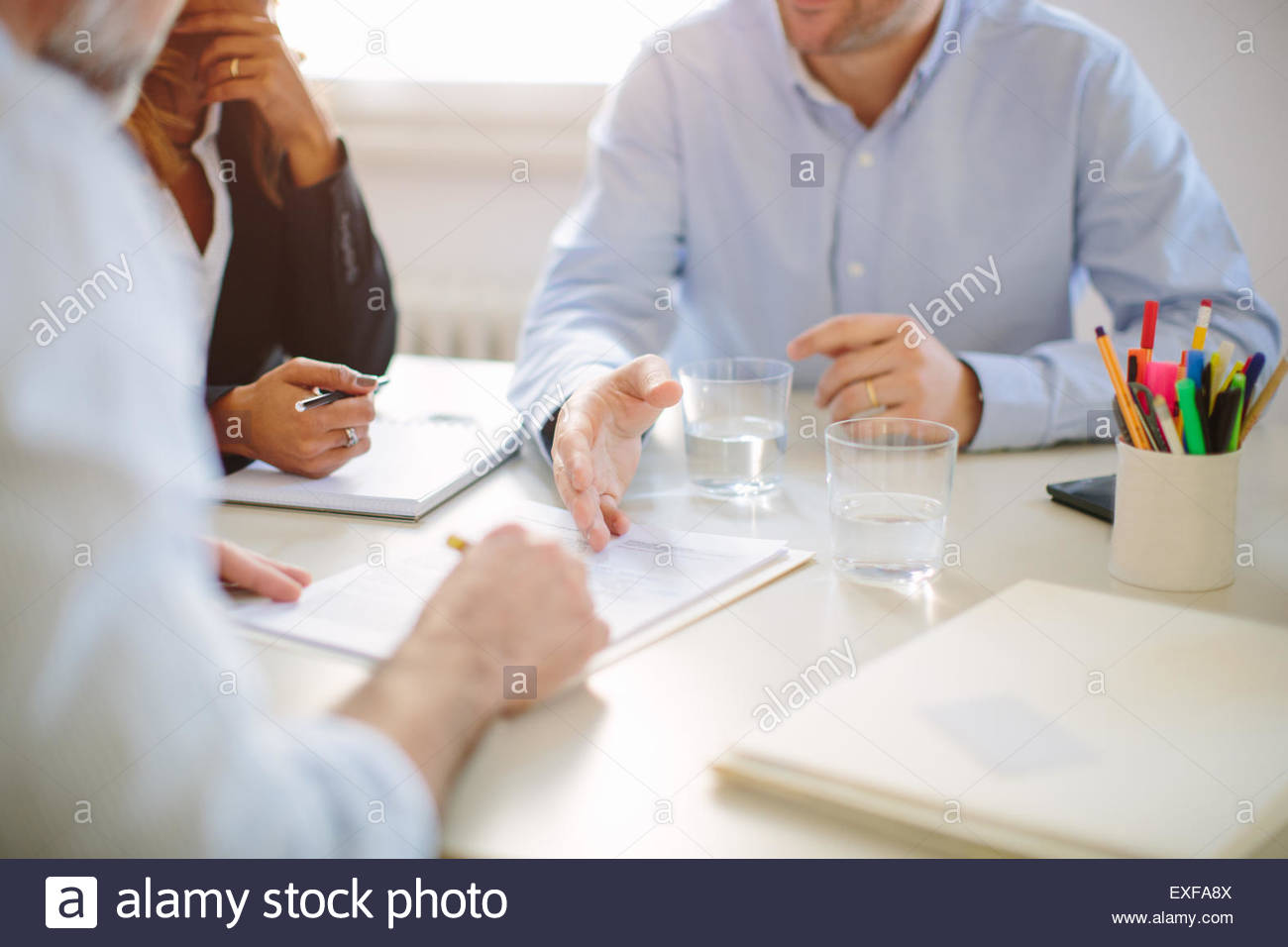 Cropped view of businessman signing contract at boardroom table - Stock Image