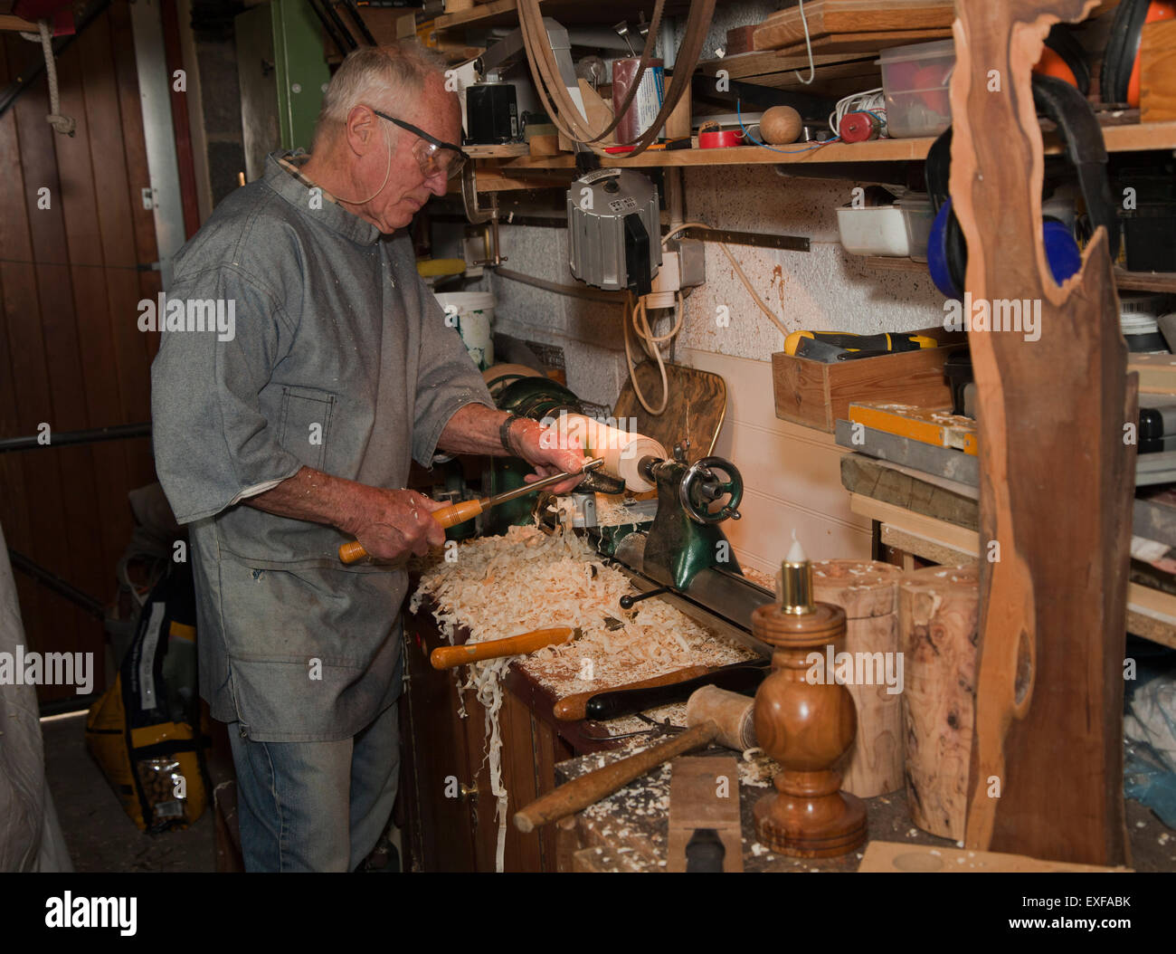 Senior man shaping piece of wood with carpentry tools - Stock Image