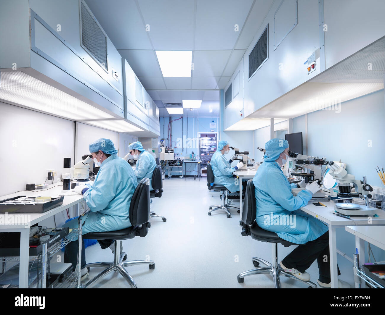 Electronics workers in clean room assembling electronic components - Stock Image