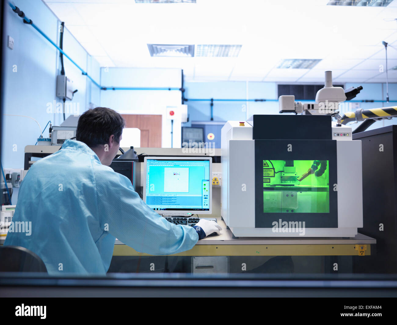 Worker operating laser marking machine in clean room laboratory - Stock Image