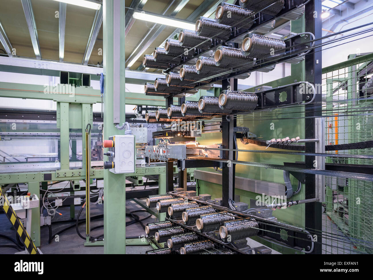 Rows of carbon fibre on loom in carbon fibre factory - Stock Image