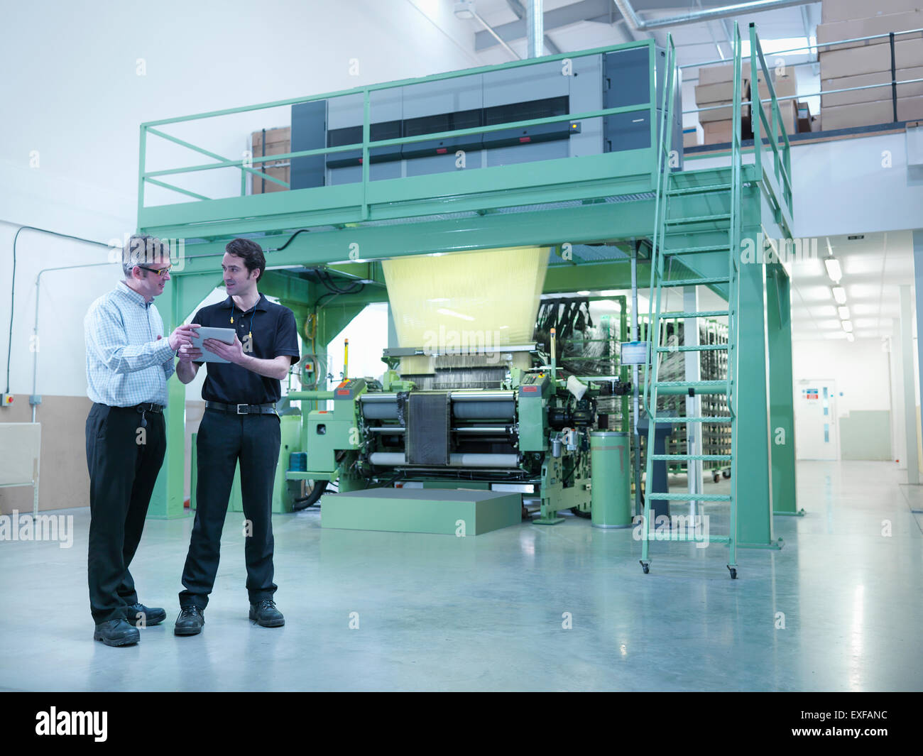 Workers using digital tablet with carbon fibre loom in carbon fibre factory - Stock Image