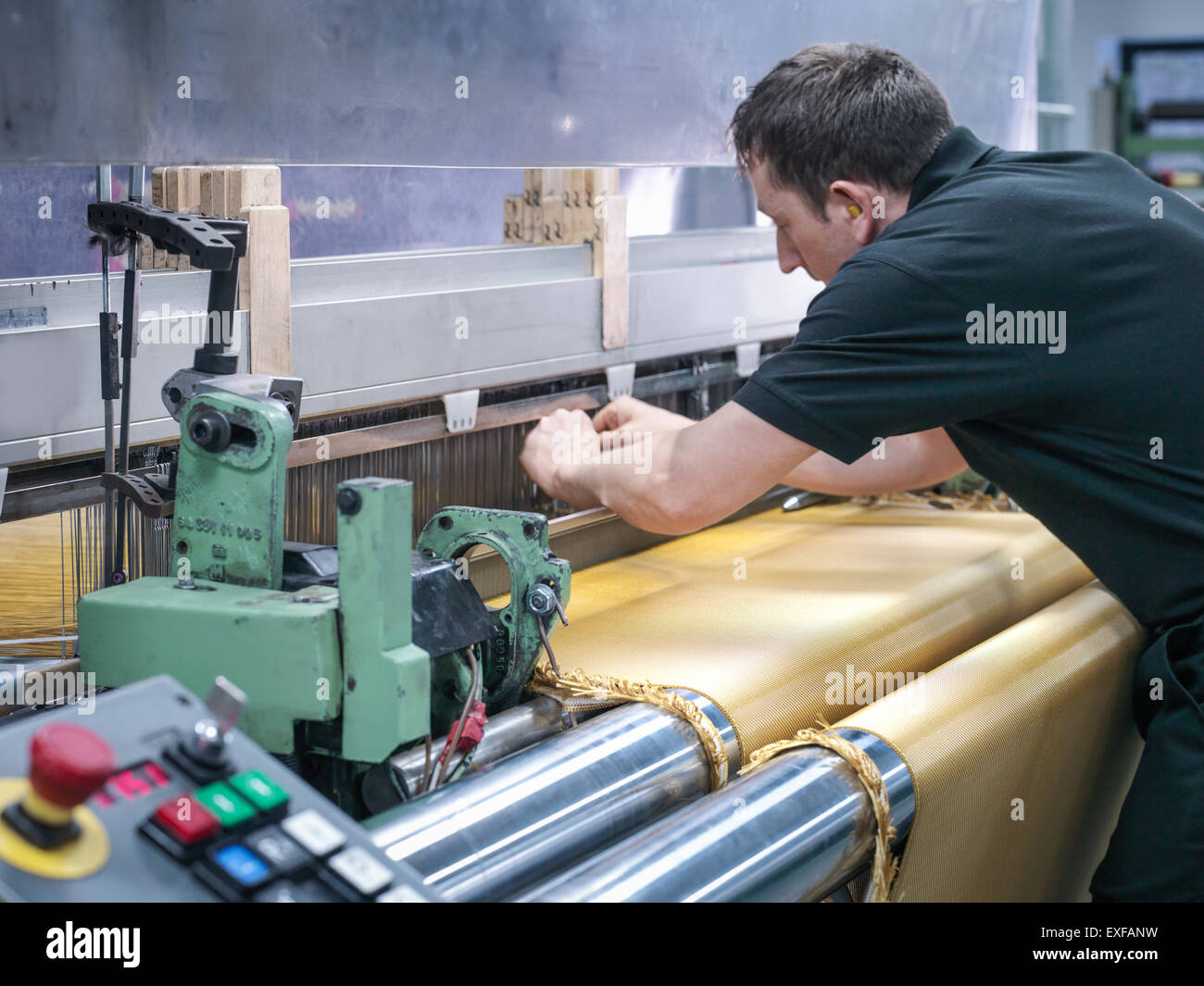 Worker weaving kevlar fabric in carbon fibre factory - Stock Image