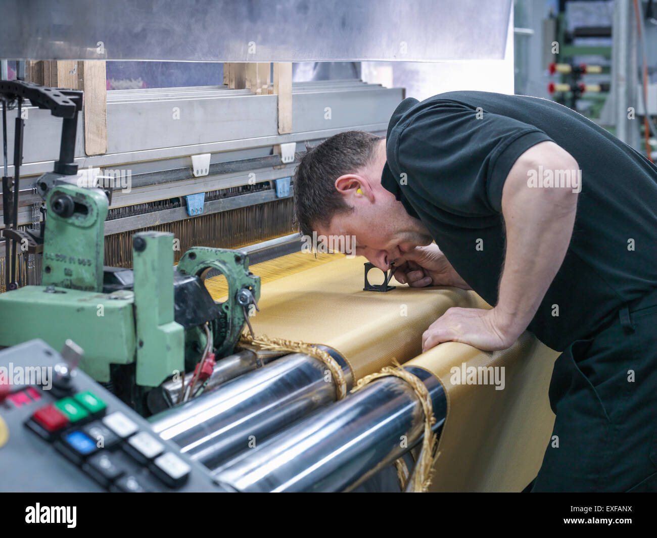 Worker inspecting kevlar fabric in carbon fibre factory - Stock Image
