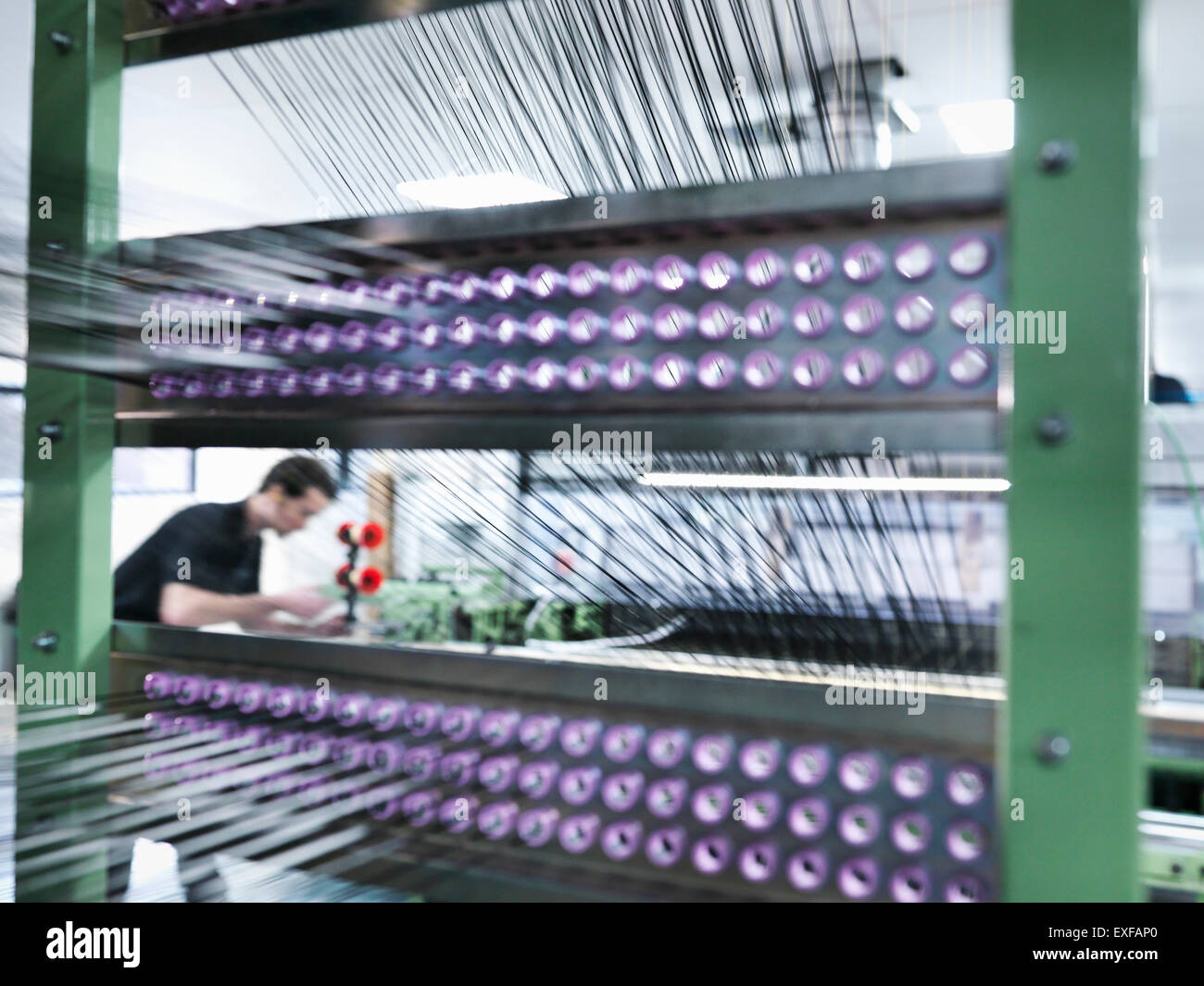 Worker weaving carbon fibre in carbon fibre factory - Stock Image