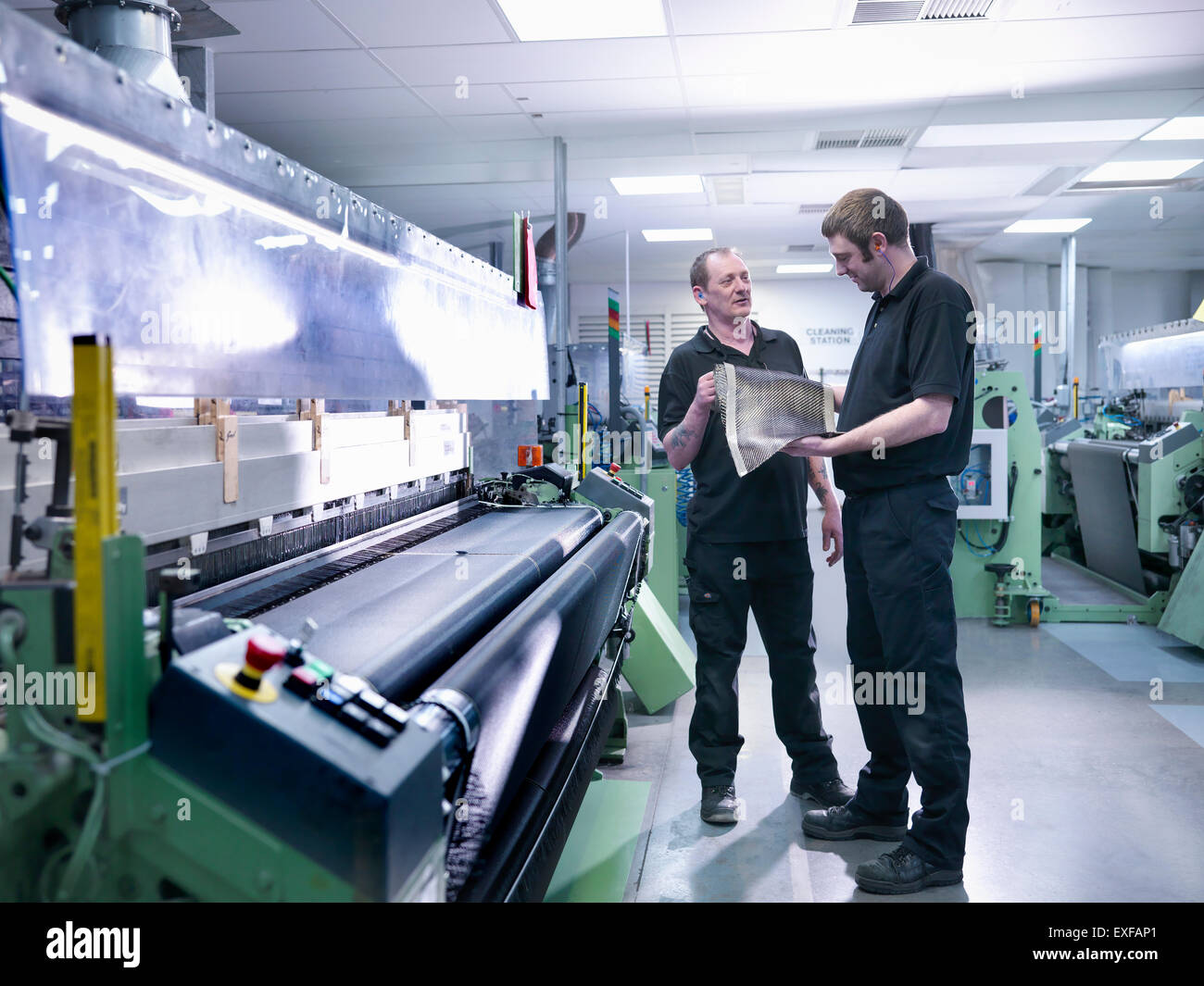 Workers inspecting carbon fibre sample in carbon fibre factory - Stock Image