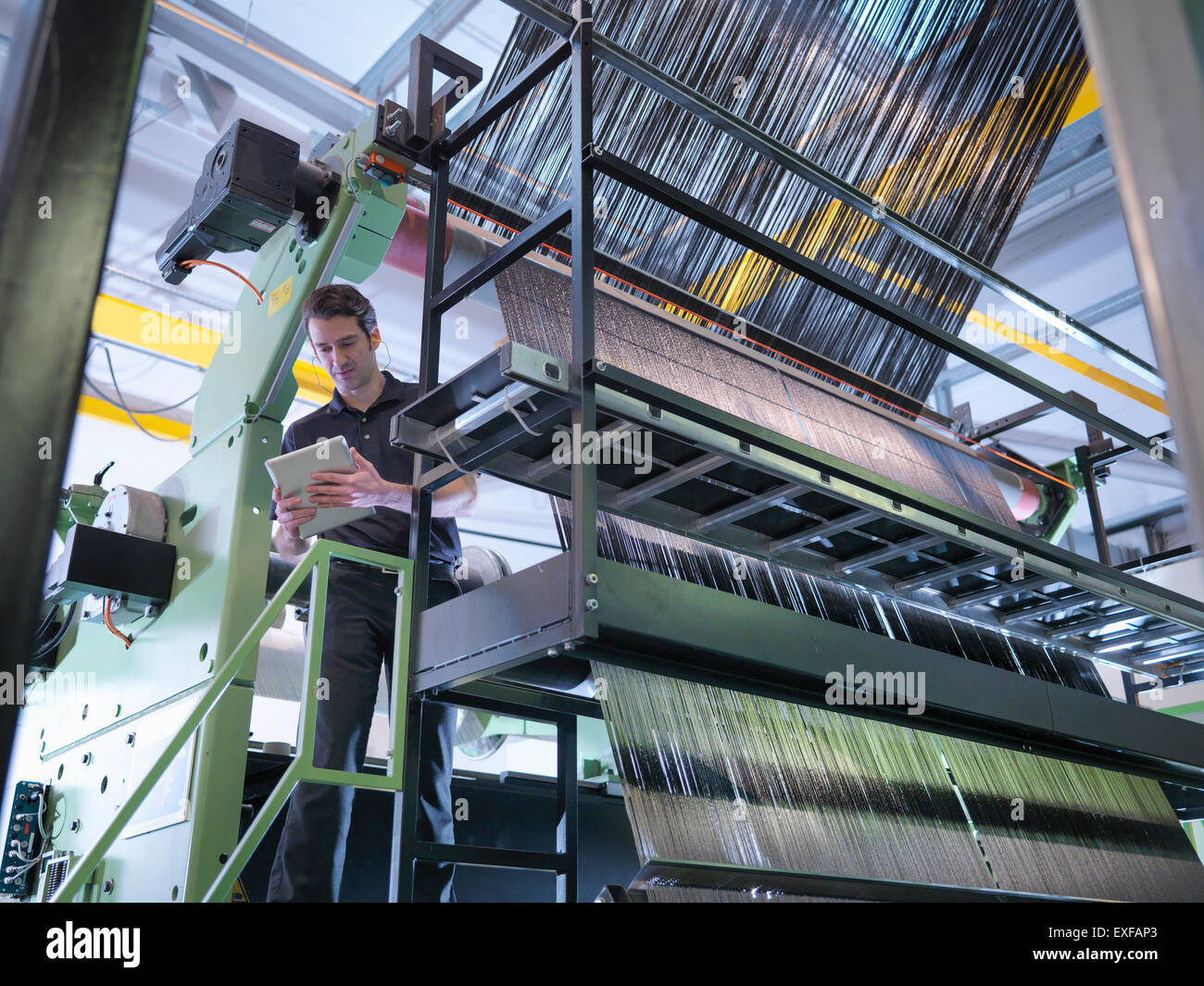 Worker inspecting carbon fibre on loom in carbon fibre factory - Stock Image