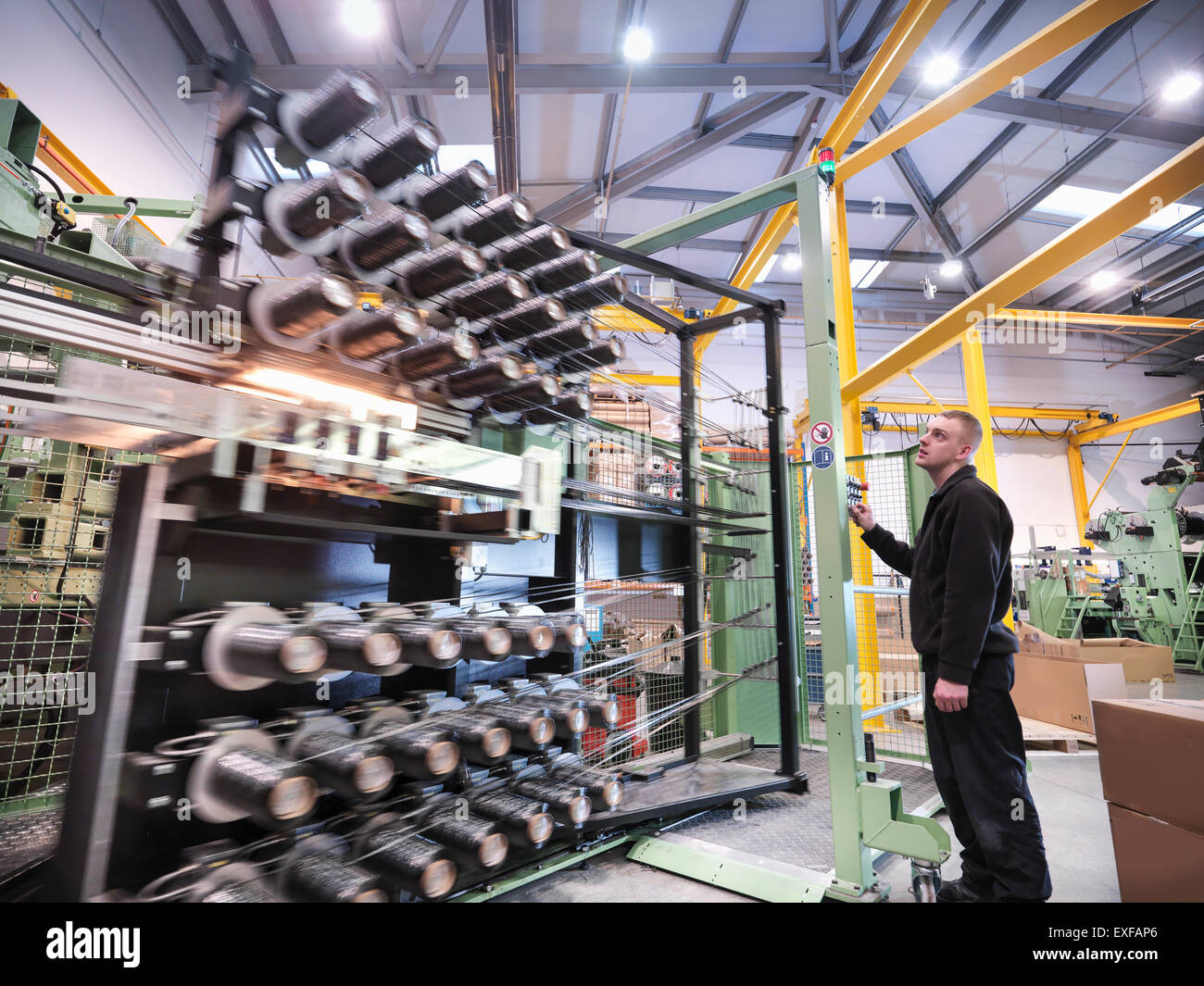 Worker operating carbon fibre loom in carbon fibre factory - Stock Image