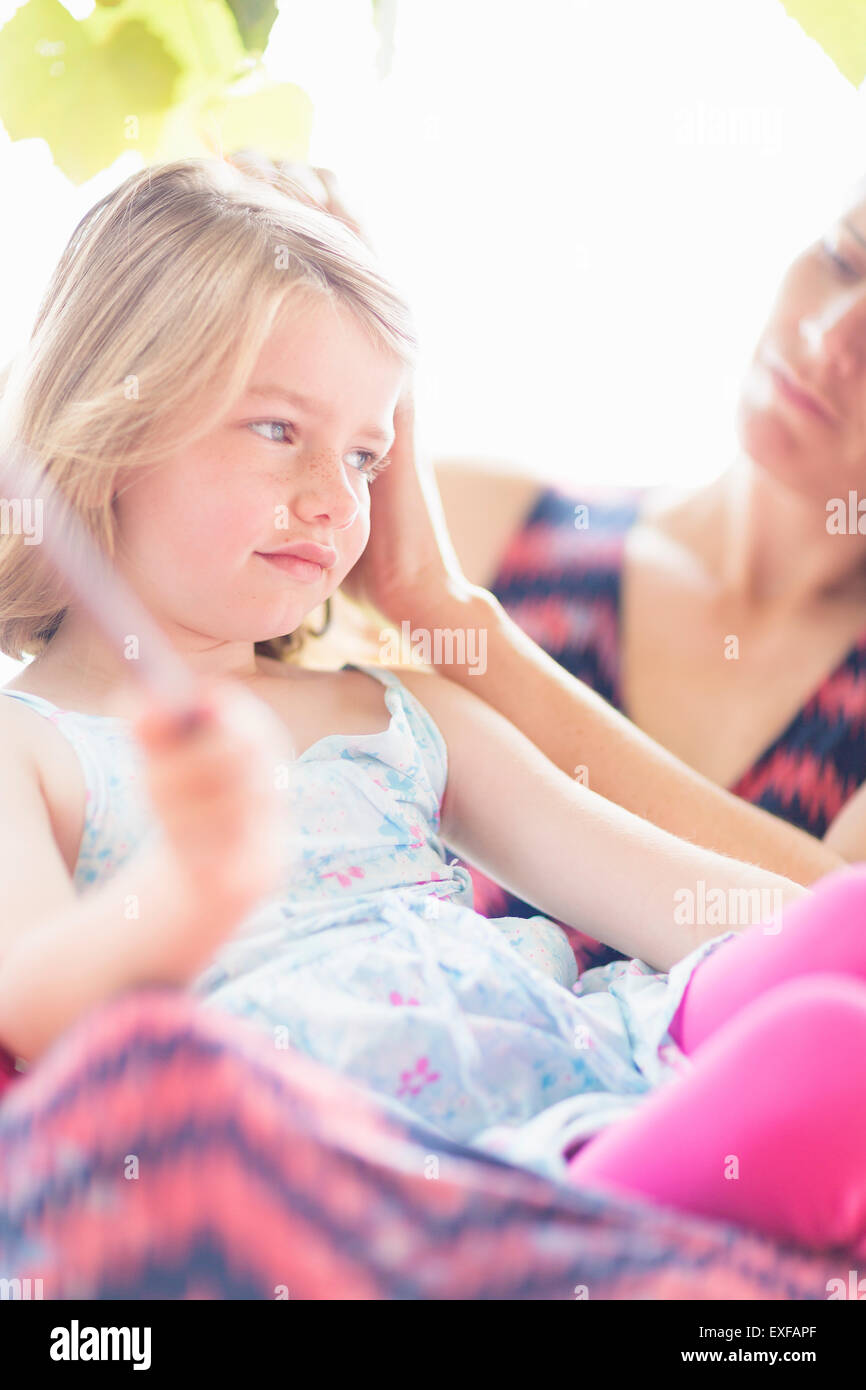 Daughter sitting on mother's lap - Stock Image