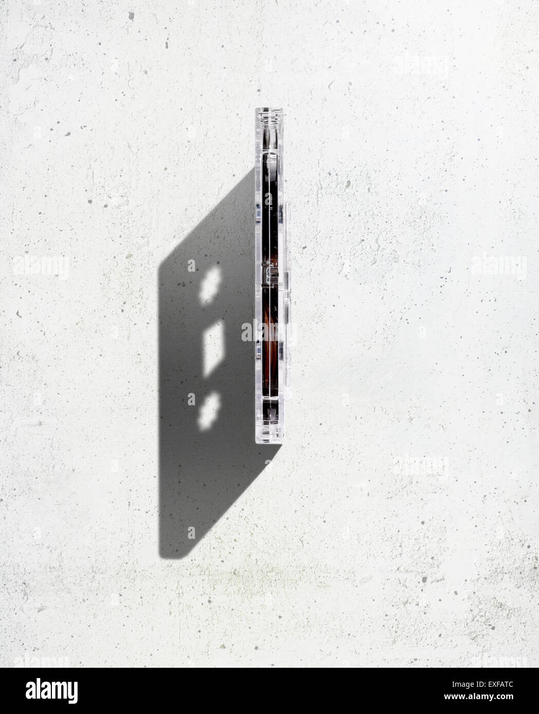 An overhead shot of an old cassette tape with a strong defining shadow. - Stock Image