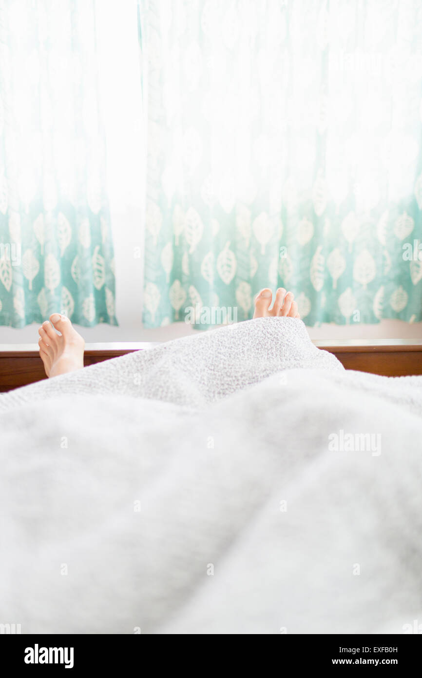 Pair of feet sticking out under duvet - Stock Image
