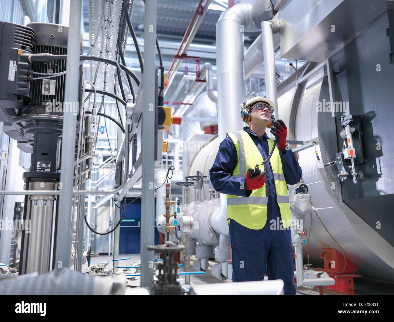Worker using radio in gas fired power station - Stock Image