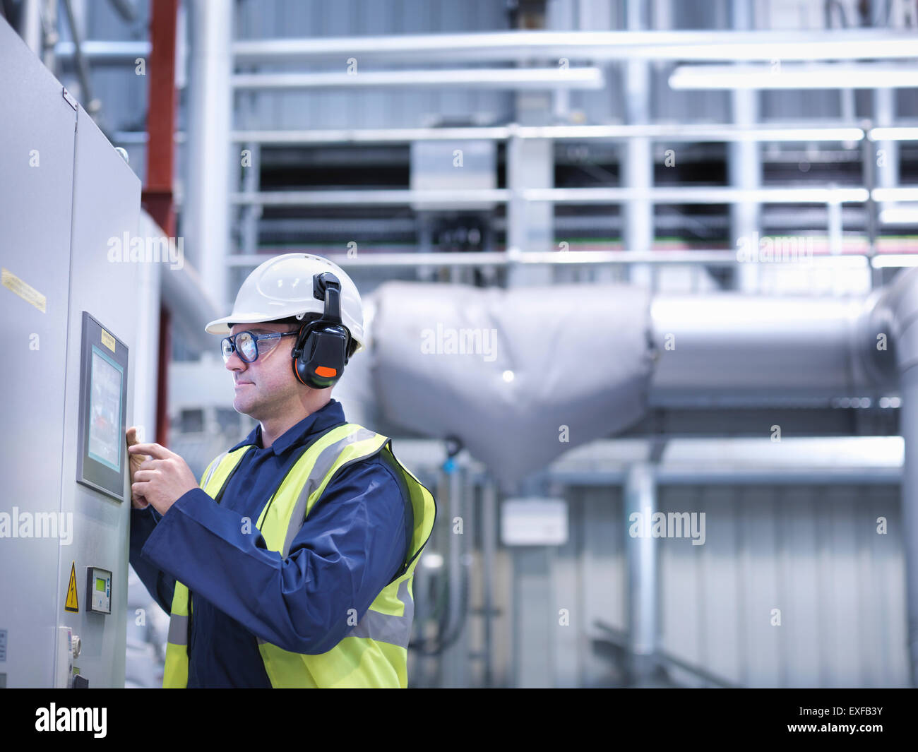 Worker using touch screen controls in gas fired power station - Stock Image