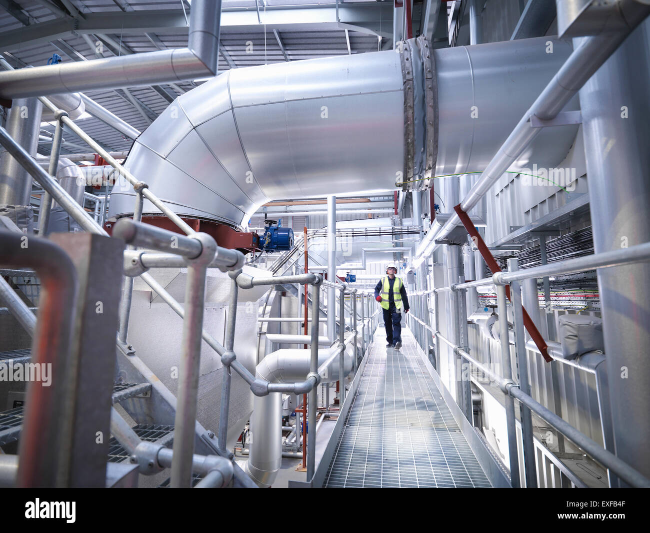 Worker on walkway in gas fired power station - Stock Image