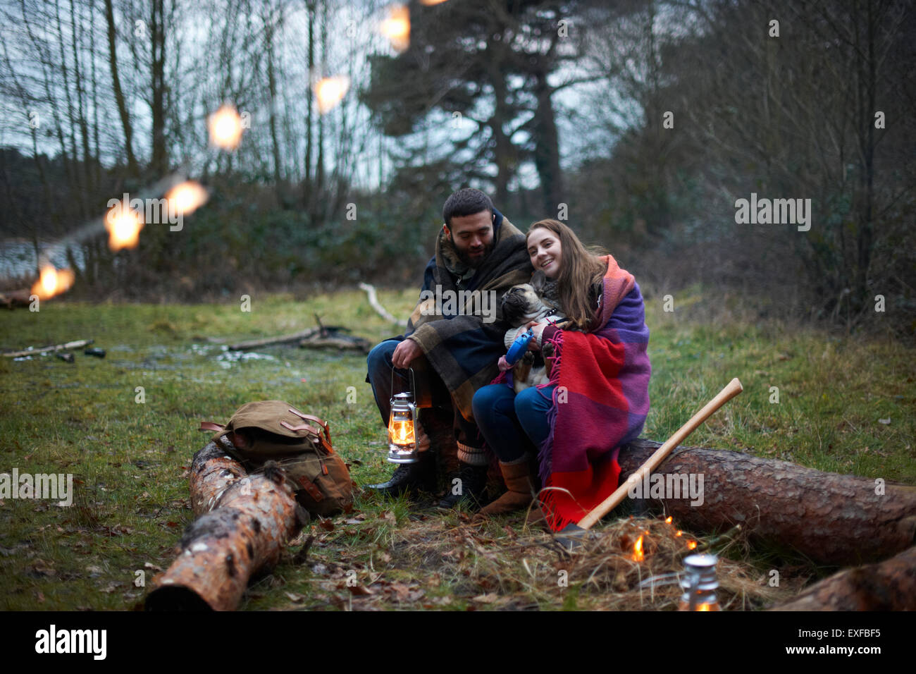 Young camping couple with dog wrapped in blanket in woods - Stock Image