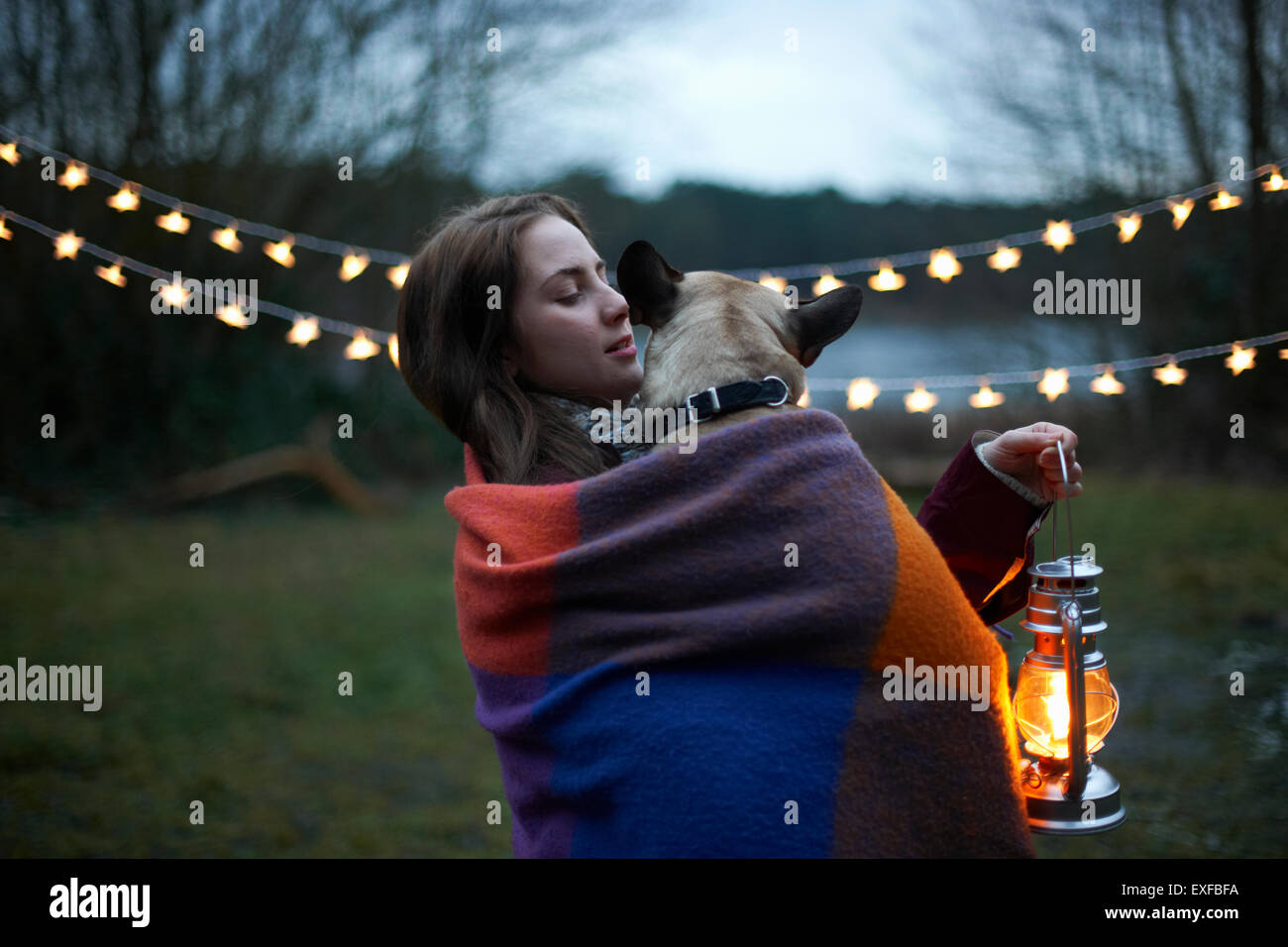 Young female camper with dog wrapped in blanket - Stock Image
