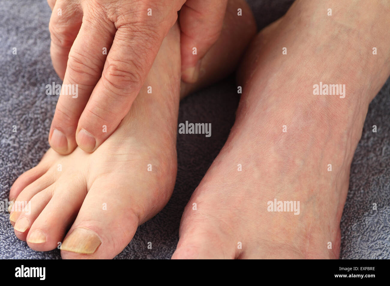 A man with his hand on one foot - Stock Image