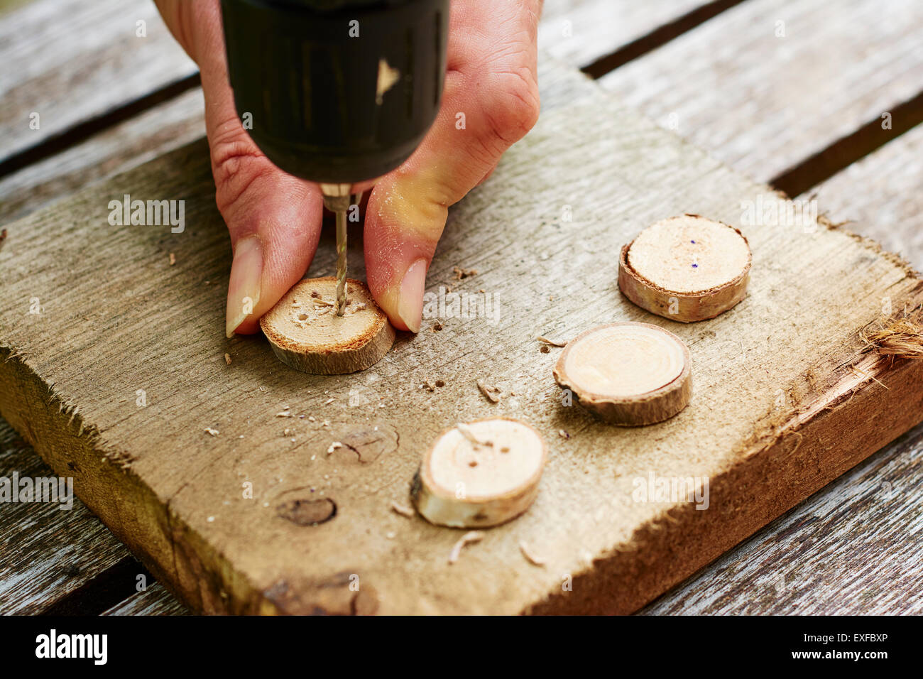 Man drilling holes into wooden buttons. - Stock Image