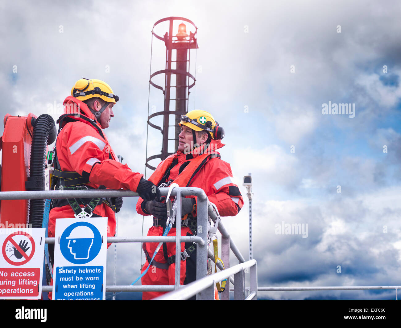 Offshore windfarm workers in discussion on jetty at sea - Stock Image