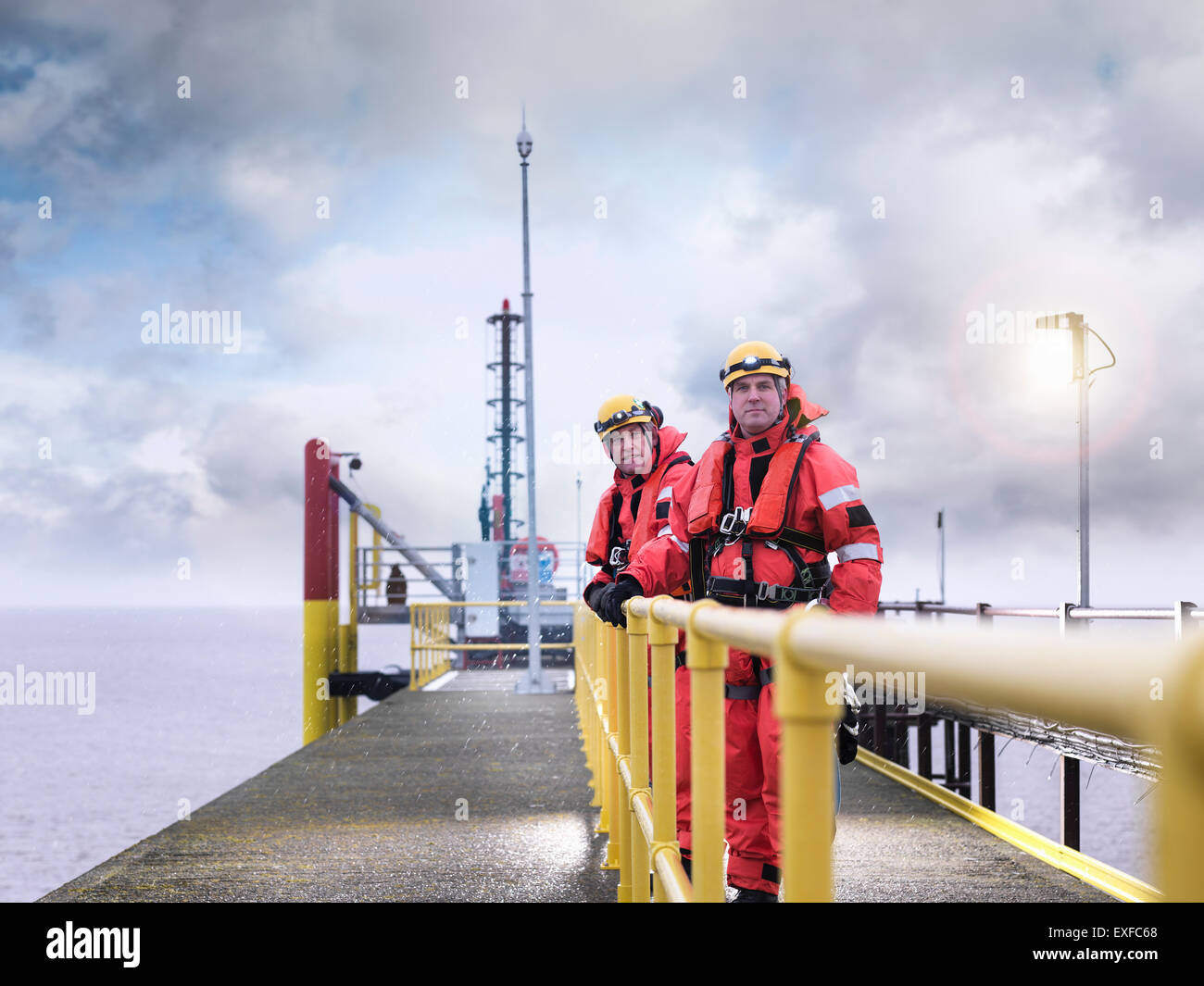 Offshore windfarm workers on jetty at sea, portrait - Stock Image