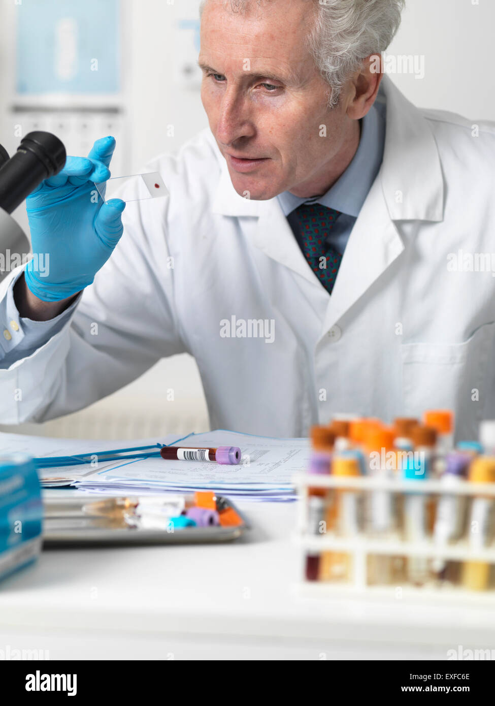 Doctor looking at patients blood slide under microscope with other samples for testing - Stock Image