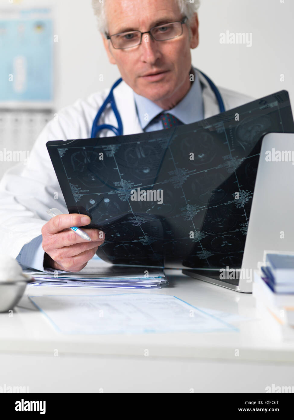Doctor studying film sheet of computed tomography (CT) scans of various sections through the human head - Stock Image